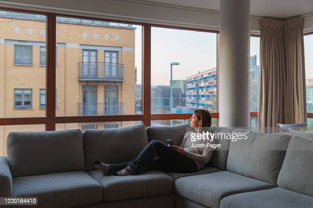 woman on sofa in apartment - looking stock pictures, royalty-free photos & images