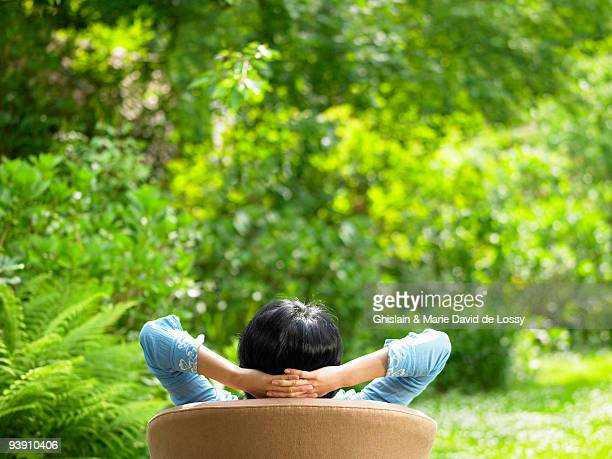 Woman on sofa, in the garden