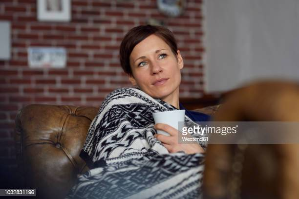 Woman on sofa relaxing at home, drinking tea