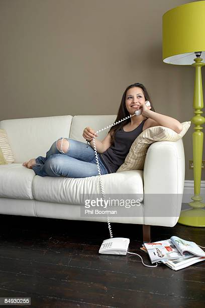 Woman on sofa using telephone