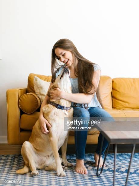 woman on sofa with dog - golden retriever photos et images de collection