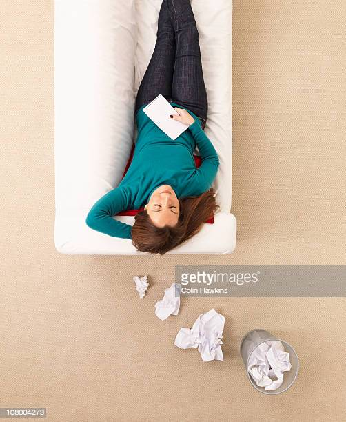 woman on sofa with paper thought bubbles - colin hawkins stock pictures, royalty-free photos & images