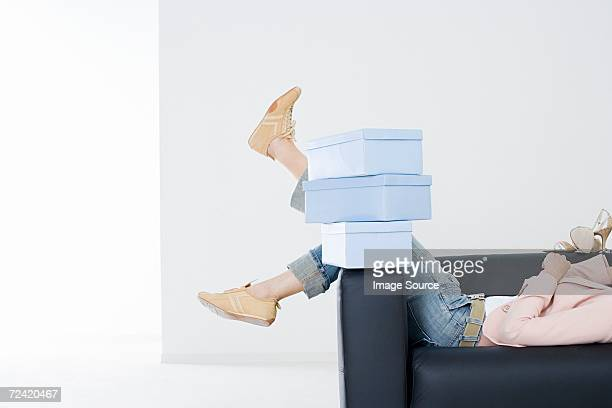 woman on sofa with shoe boxes - シューズボックス ストックフォトと画像