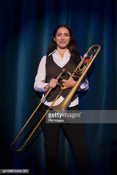 Woman on stage holding trombone, smiling, portrait