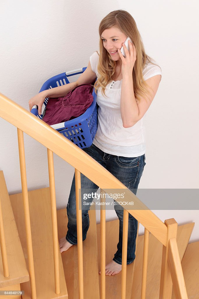 Woman On Stairs With Laundry Basket And Cell Phone