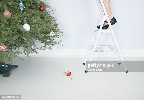 Woman on step ladder beside Christmas tree, broken ornament on floor