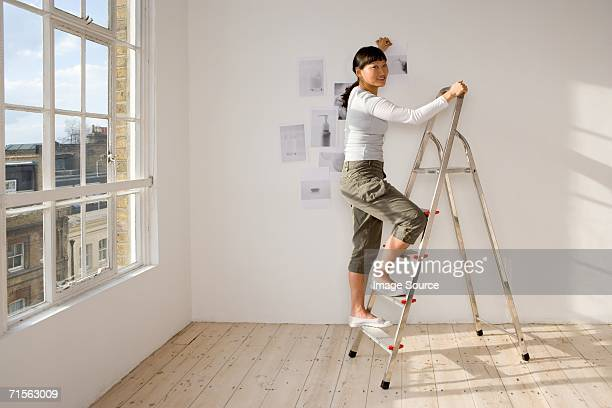 woman on stepladder putting up pictures - step ladder stock photos and pictures