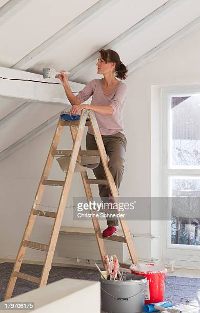 Woman on stepladders painting white ceiling