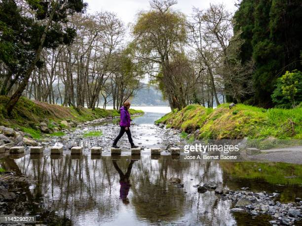 Woman on Stepping Stones in a River.  Island of Sao Miguel, Azores Islands, Portugal. Europe