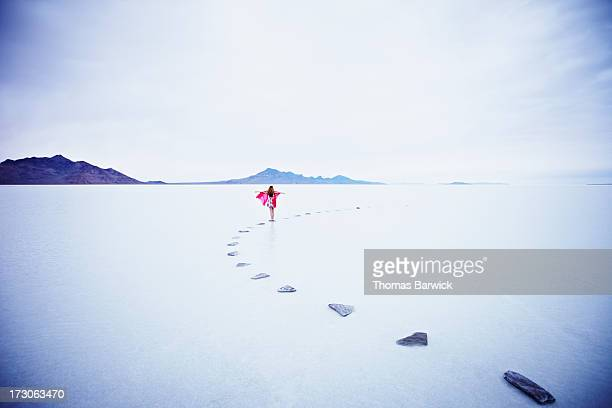 Woman on stone pathway in lake with arms out