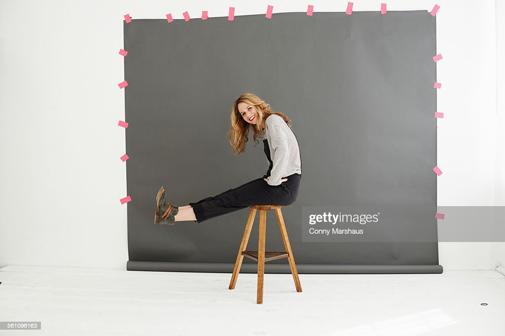 Woman on stool in front of photographers backdrop : Stock Photo