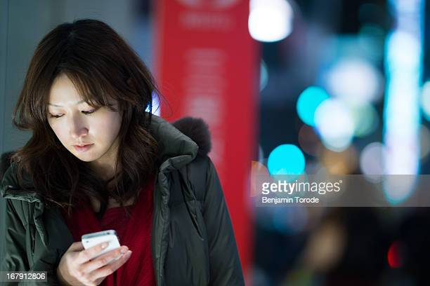 Woman on street at night using white smartphone