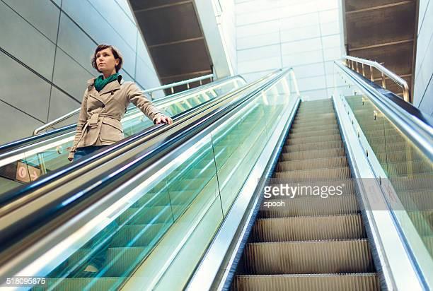 Woman on subway station escalator in Copenhagen, Denmark.