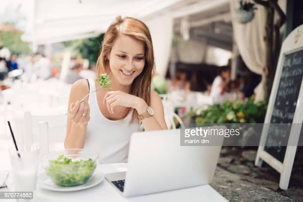 Kvinna på sommarlovet äta i restaurangen och arbetar på bärbar dator