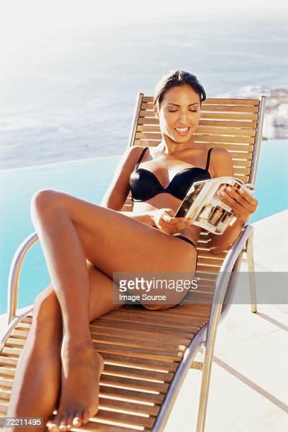 Woman on sun lounger reading a magazine