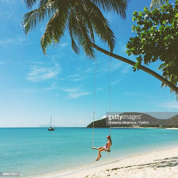 woman on swing at calm beach - ko samui stock photos and pictures