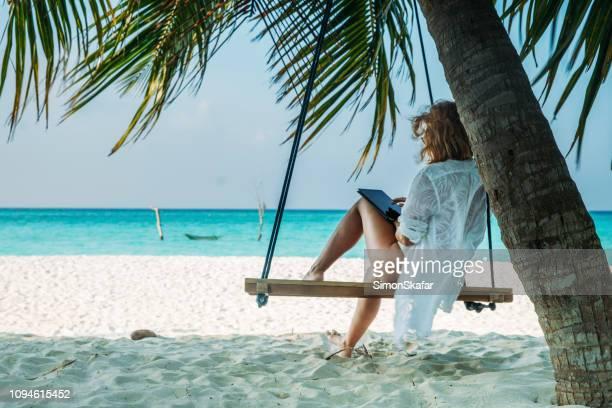 mujer en columpio colgado de la palmera en la playa de arena con tableta, maldivas - espalda chica morena playa fotografías e imágenes de stock