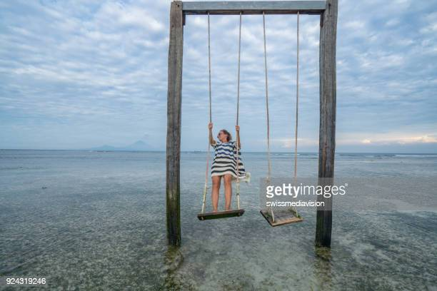 woman on swing over sea, vacations - gili trawangan stock photos and pictures