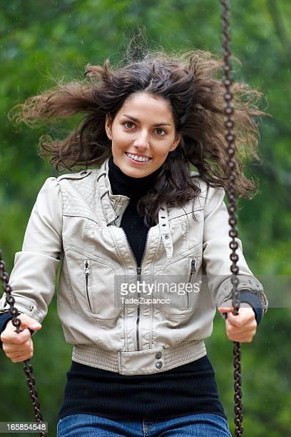 Lächelnde Frau auf Schaukel