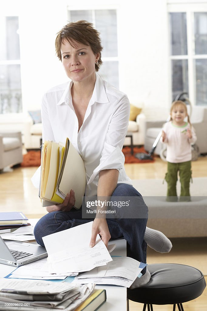 Woman On Table Holding Papers Daughter In Background Portrait High Res Stock Photo Getty Images