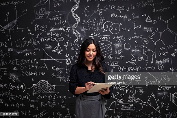 Woman on tablet with math chalkboard