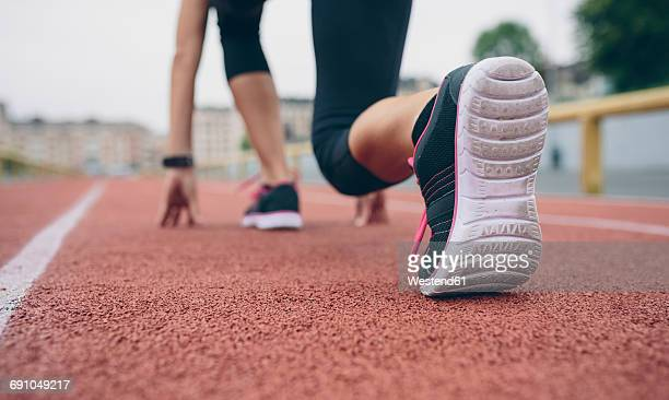 Woman on tartan track in starting position