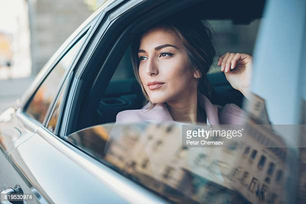 woman on the back seat of a car - stereotypically upper class stock pictures, royalty-free photos & images
