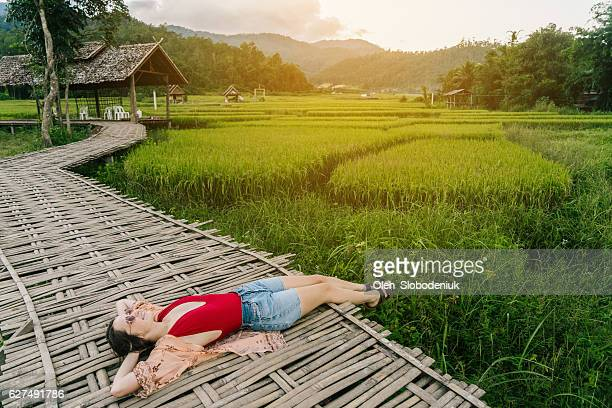 Woman on the bamboo bridge near the rice field