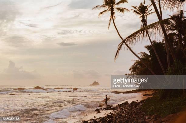 Woman on the beach with surfboard in Sri Lanka
