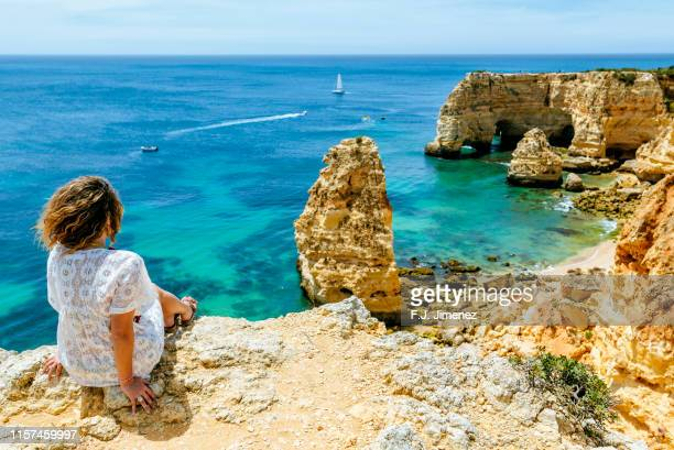 woman on the cliffs looking towards at praia da marinha - algarve fotografías e imágenes de stock