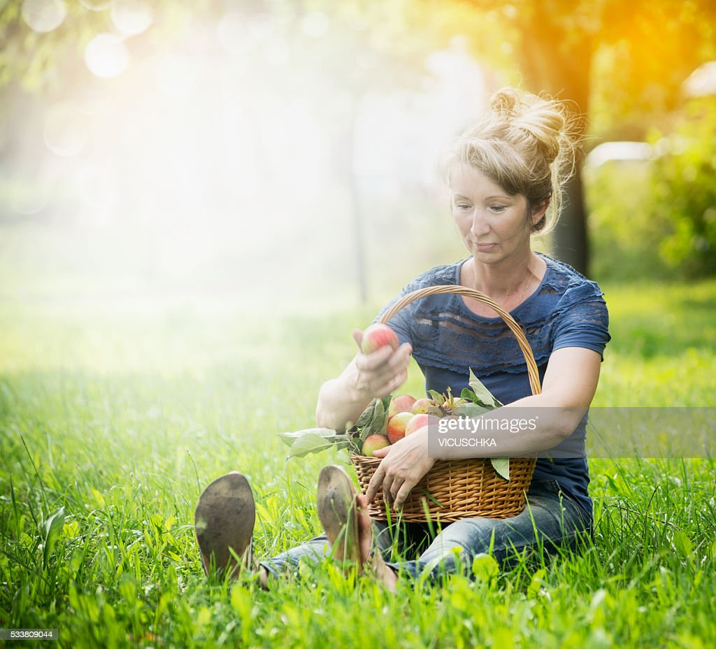 Woman on the grass with basket of apples on her lap : Foto stock
