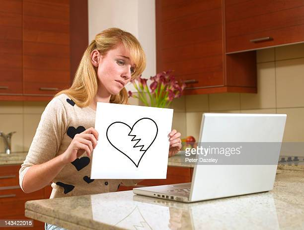 woman on the internet with a broken heart sign - negative emotion stock pictures, royalty-free photos & images