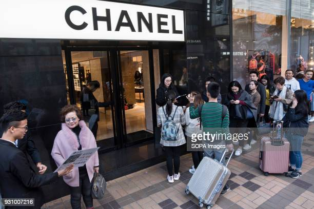Woman, on the left, is approached by property agents while on the right hand side shoppers and tourists wait in line at Chanel store. Tsim Sha Tsui's...