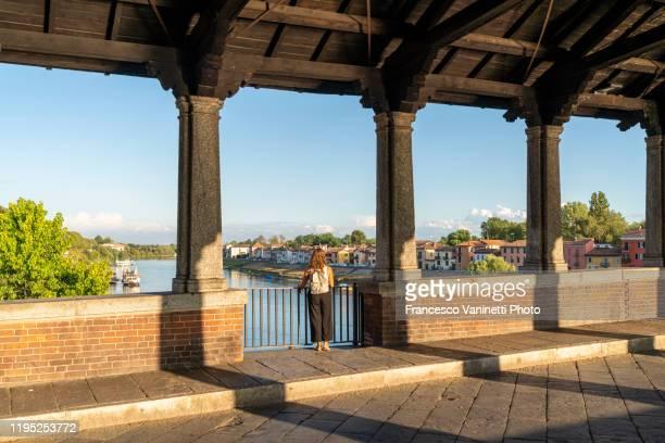 woman on the old bridge gazing at borgo ticino district, pavia, italy. - イタリア パヴィア ストックフォトと画像
