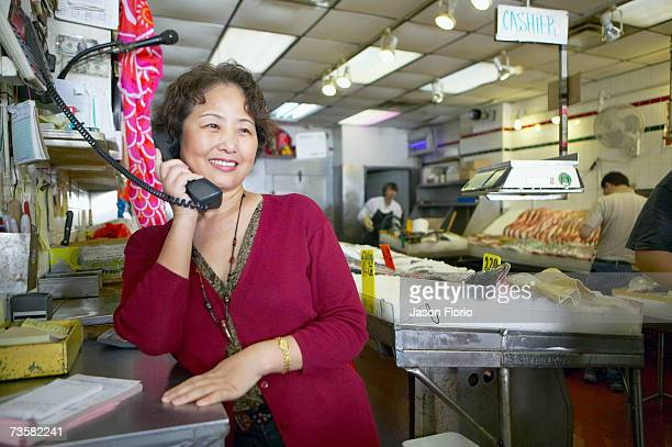 Woman on the phone at fish market, smiling