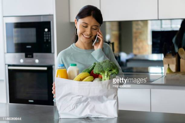 woman on the phone at home unpacking the groceries after shopping - grocery delivery stock pictures, royalty-free photos & images