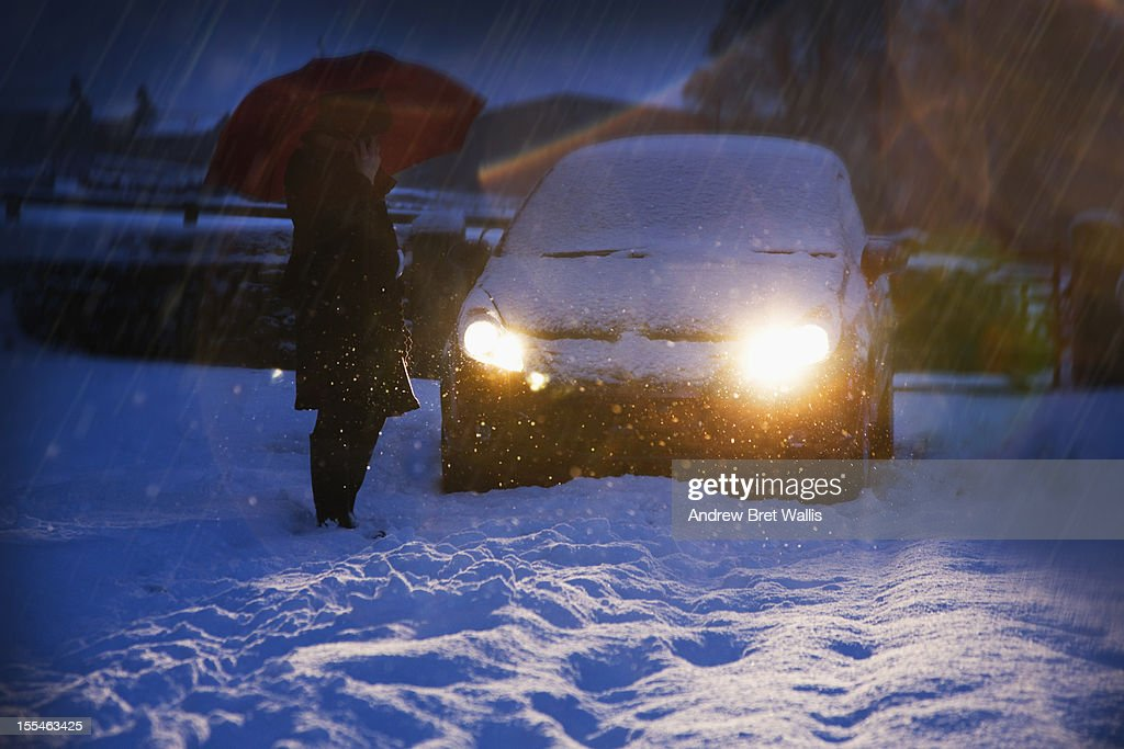 A woman on the phone beside a car in snow at night : Stock Photo