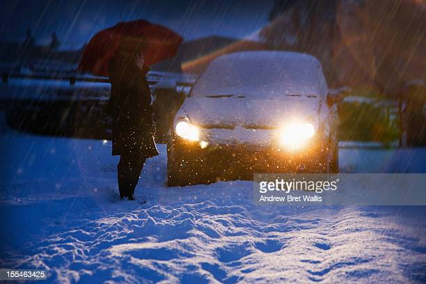 A woman on the phone beside a car in snow at night