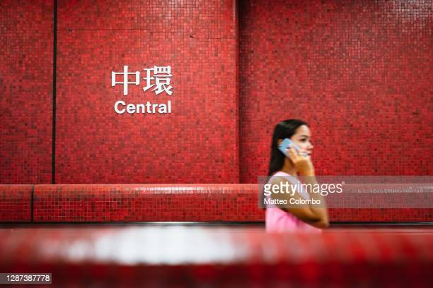 woman on the phone in subway station, hong kong - hong kong stock pictures, royalty-free photos & images
