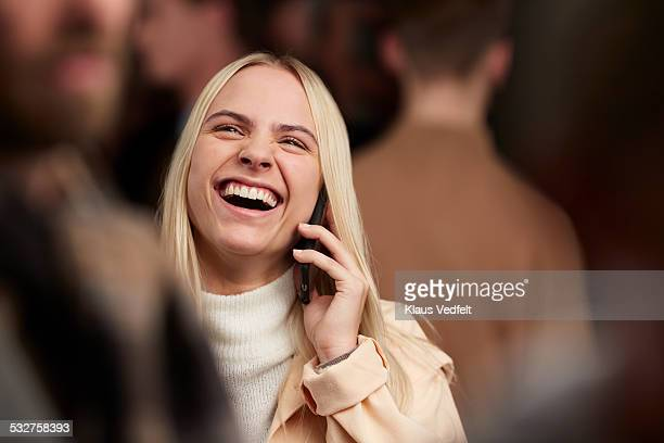 Woman on the phone laughing, among crowd