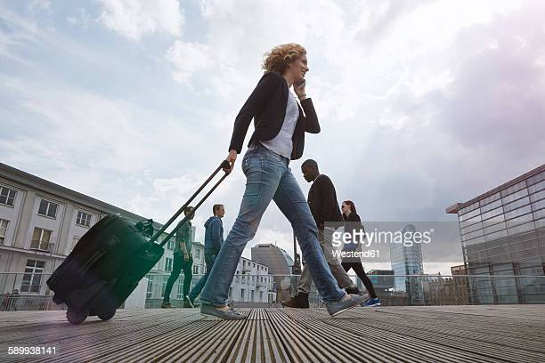 Woman on the phone walking with a rolling suitcase in the city