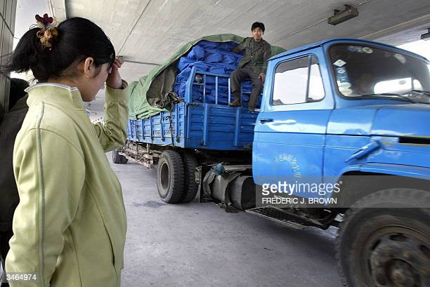 Woman on the platform of Dandong railway station in China's northeast Liaoning Province reacts as a truck carrying supplies bound for the disaster...