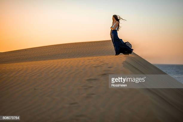 woman on the sand dunes - windy skirt stock photos and pictures