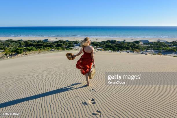 woman on the sand goes to the sea on foot. - kas stock pictures, royalty-free photos & images