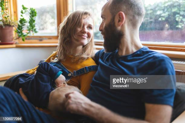 woman on the sofa breastfeeding her little son and sharing time with her husband - love stock pictures, royalty-free photos & images