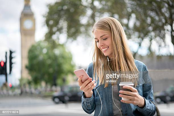Woman on the street listening to music on her phone