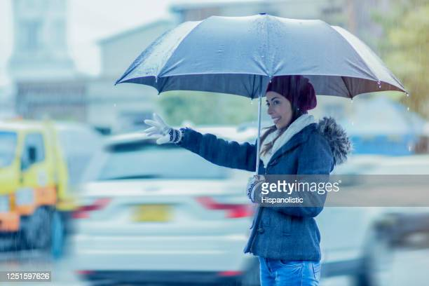 woman on the street trying to get a taxi on a rainy day - catching stock pictures, royalty-free photos & images