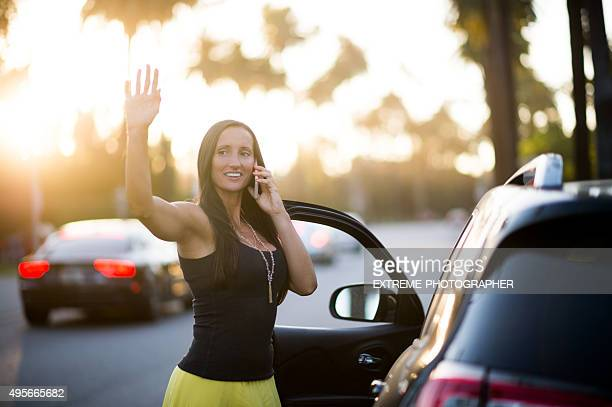 Woman on the street waving to someone