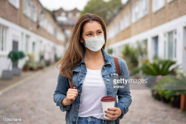 woman on the street wearing a facemask and holding a coffee to go - protective face mask stock pictures, royalty-free photos & images