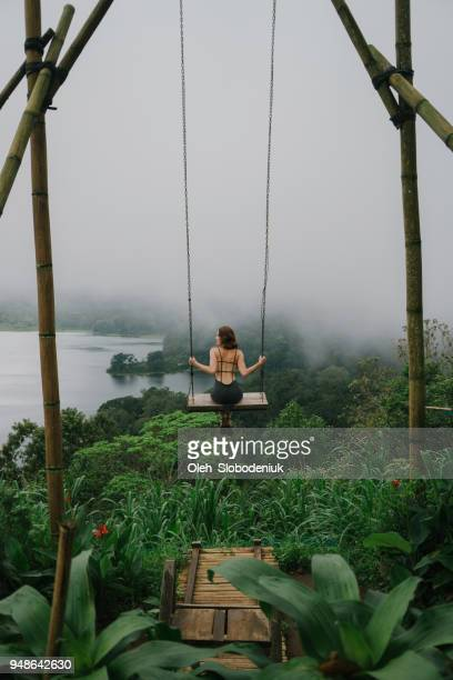 woman on the swing over the jungles and lake  in bali - vertical stock pictures, royalty-free photos & images